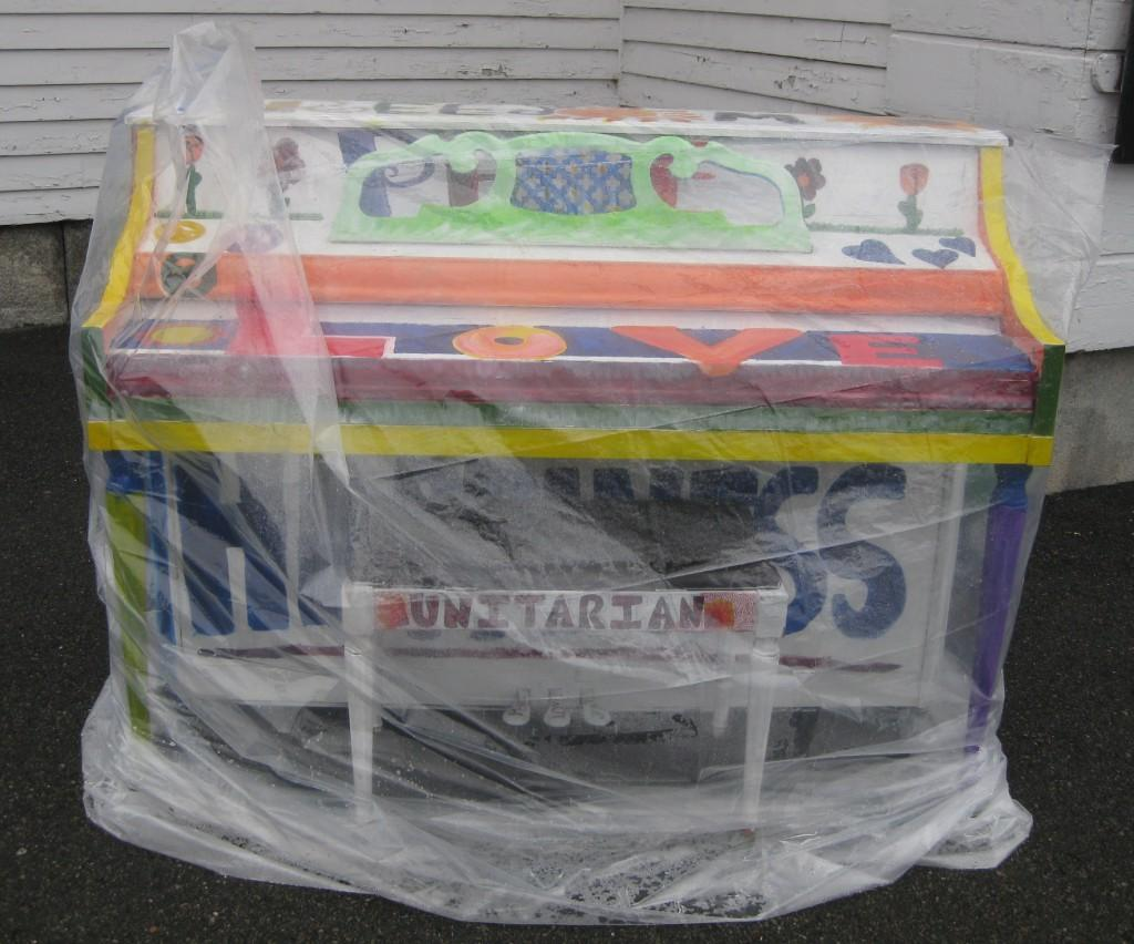 Plastic covers and protects the peace, love, and hope piano from rain in front of the Unitarian church. | by Stephanie Petrovick